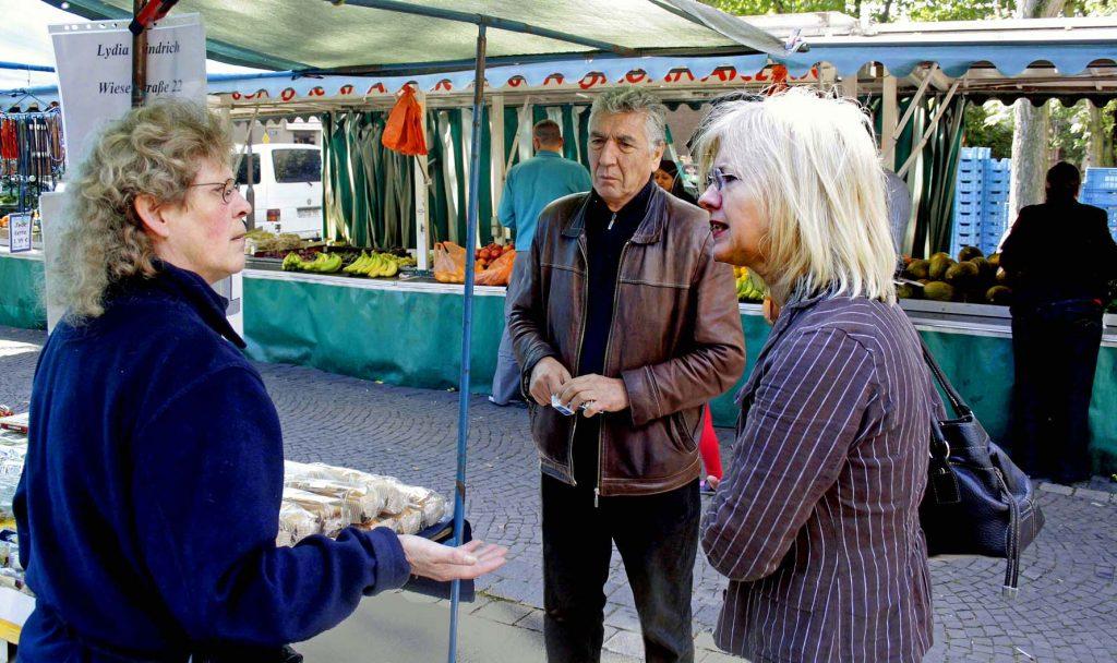 """Markthändlerin Lydia Windrich (links) spricht mit ihrem türkischen Bekannten Ibrahim Kartal und seiner Lebensgefährtin Sabine Hoster über die vermeintlichen """"Sprachbarrieren""""."""
