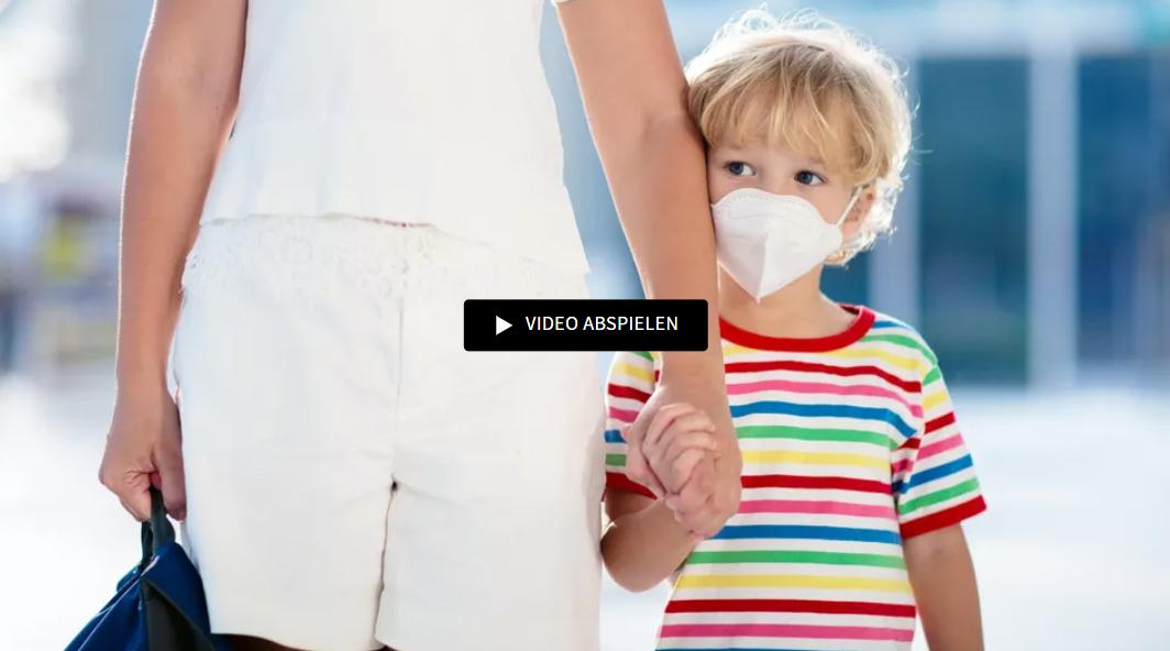 Kleines Kind mit Maske an Hand der Mutter